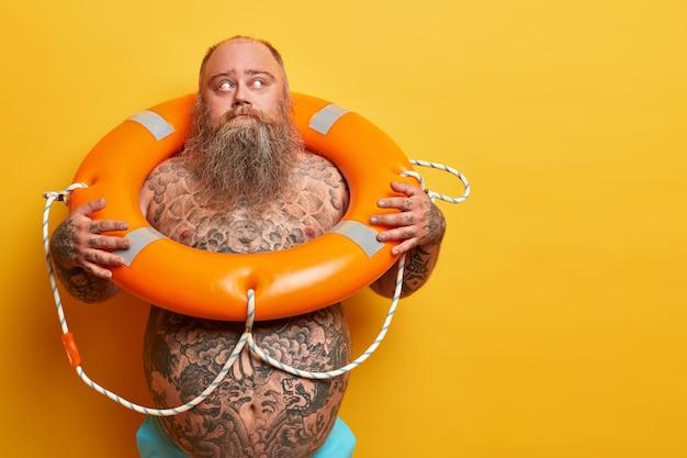Tiro interno de homem com excesso de peso pensativo desvia o olhar, pronto para recreação, nadando no mar com bóia salva-vidas, corpo nu, isolado na parede amarela, espaço em branco à parte equipamento de segurança, resgate