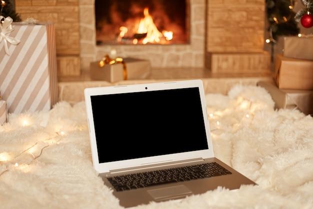 Tiro interno de laptop com tela em branco com copyspace para anúncio ou texto promocional no tapete macio branco no chão perto da lareira na sala de estar.