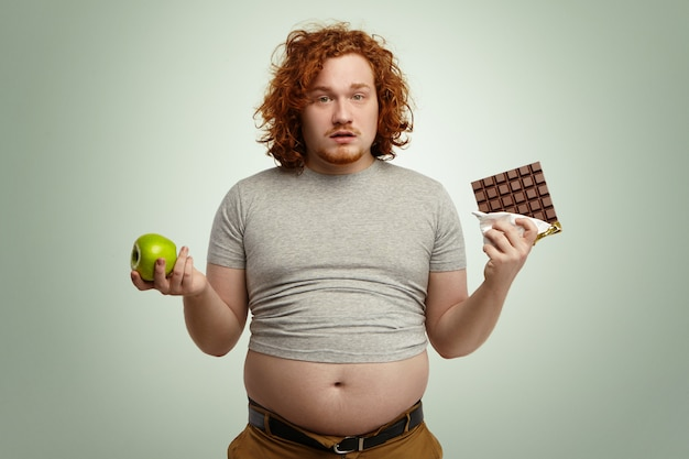 Tiro interno de macho jovem gordo confuso e incerto, enfrentando uma escolha difícil, pois ele tem que escolher entre maçã orgânica fresca em uma mão e deliciosa barra de chocolate na outra. dilema, dieta e alimentação