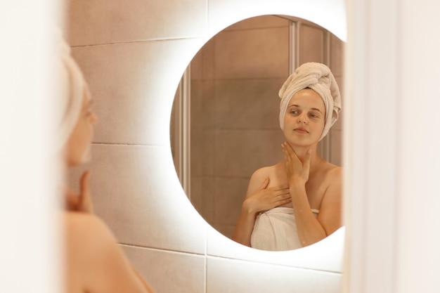 Tiro interno de mulher bonita olhando no reflexo no espelho depois do banho, tocando seu pescoço, fazendo procedimentos matinais, apreciando seu olhar fresco.