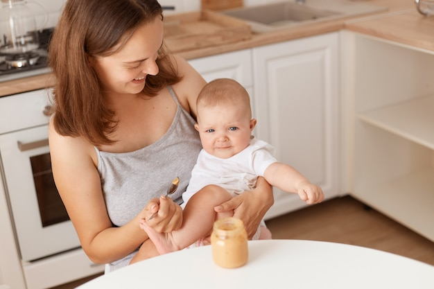Tiro interno de mulher de cabelos escuros alimenta sua filha com purê de frutas ou vegetais, mãe olhando para seu bebê fofo com amor, alimentação saudável.