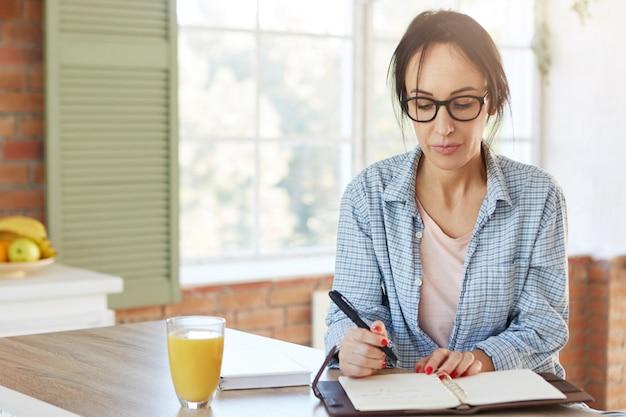 Tiro interno de mulher europeia séria segura a caneta, escreve informações que ela encontrou na internet ou livro no caderno, senta-se à mesa da cozinha de madeira com suco.