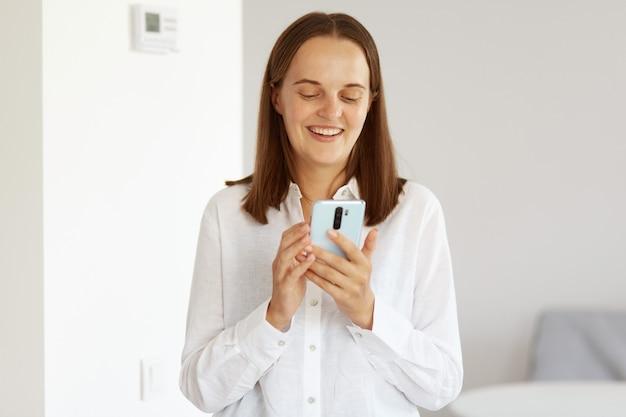 Tiro interno de mulher feliz positiva com cabelo escuro, posando em uma sala clara em casa, vestindo uma camisa branca estilo casual, olhando para o visor do telefone inteligente, tendo uma chamada de vídeo ou transmissão ao vivo.