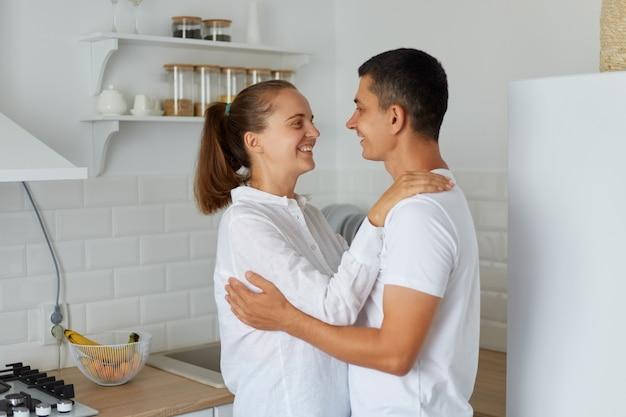 Tiro interno de mulher sorridente, abraçando-se com o marido em casa na cozinha leve, casal feliz juntos e olhando um para o outro com sentimentos românticos e amor.