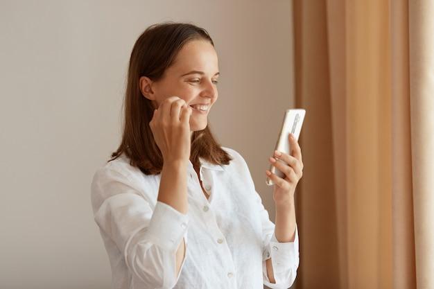 Tiro interno de mulher sorridente feliz com cabelo escuro, vestindo uma camisa de algodão branco em pé na sala clara perto da janela com cortinas bege, segurando o telefone inteligente e tem chamada de vídeo.