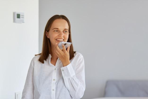 Tiro interno de mulher sorridente feliz posando em casa, numa sala de luz, vestindo roupas brancas, segurando o telefone inteligente nas mãos e gravando a massagem de voz ou usando o assistente de voz.