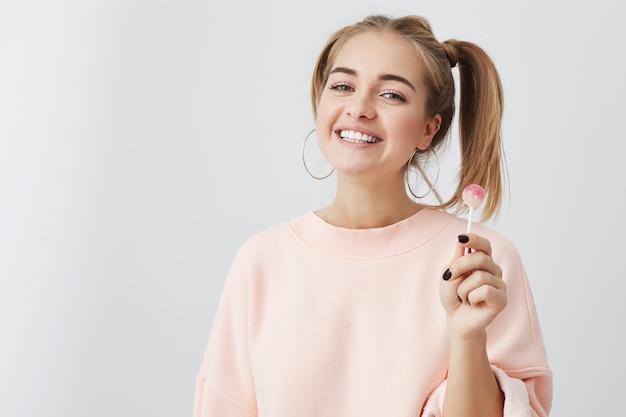 Tiro interno do adolescente consideravelmente positivo com dois rabos de cavalo, olhos escuros atraentes e pele pura saudável, sorrindo amplamente demonstrando seus dentes perfeitos brancos, isolados no fundo cinzento do estúdio.