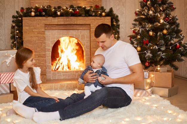 Tiro interno do jovem adulto caucasiano pai sentado no chão com duas filhas perto da lareira e da árvore de natal, celebrando juntos as férias de inverno.