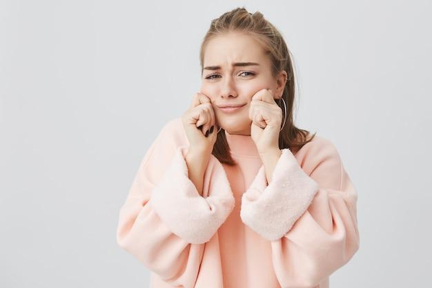 Tiro isolado da encantadora loira caucasiana em roupas cor de rosa, beliscando as bochechas, mostrando o quão grandes elas são. engraçado fêmea zombando e posando dentro de casa.