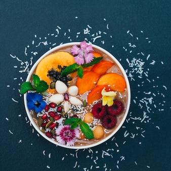 Tiro isolado da tigela com frutas tropicais, decorado com flores, hortelã, flocos de coco isolados sobre fundo azul escuro. caqui fresco, framboesa e amêndoa.