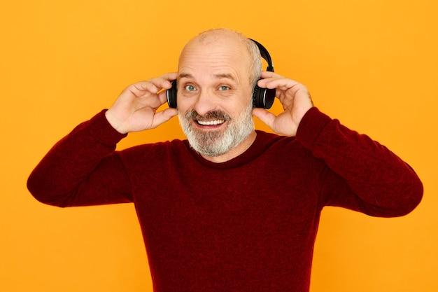 Tiro isolado de alegre homem sênior caucasiano com cabeça careca e barba grisalha sorrindo assumindo wireless moderno conectando-os ao dispositivo eletrônico via bluetooth.