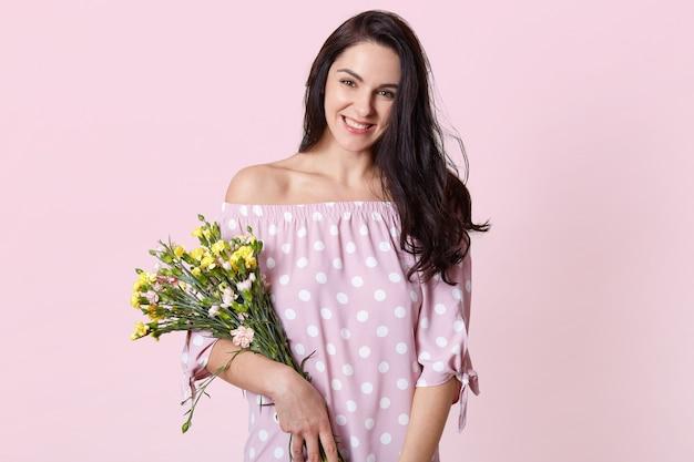 Tiro isolado de alegre mulher de cabelos escuros usa vestido de verão de bolinhas, mantém o buquê de flores, mostra ombros nus