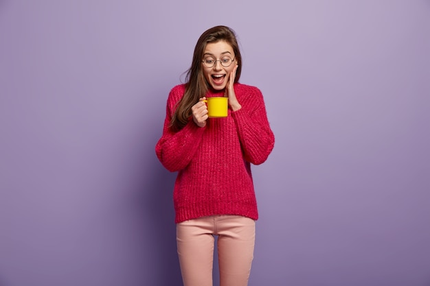 Tiro isolado de mulher radiante feliz olha para o copo de bebida aromática quente, segura a caneca amarela, usa óculos, jumper vermelho, fica contra a parede roxa. mulher alegre tem pausa para o café. conceito de bebida