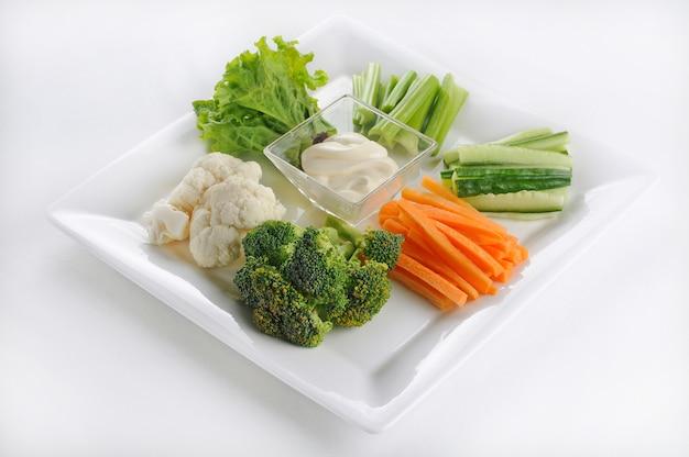 Tiro isolado de um prato branco com legumes fatiados com molho branco