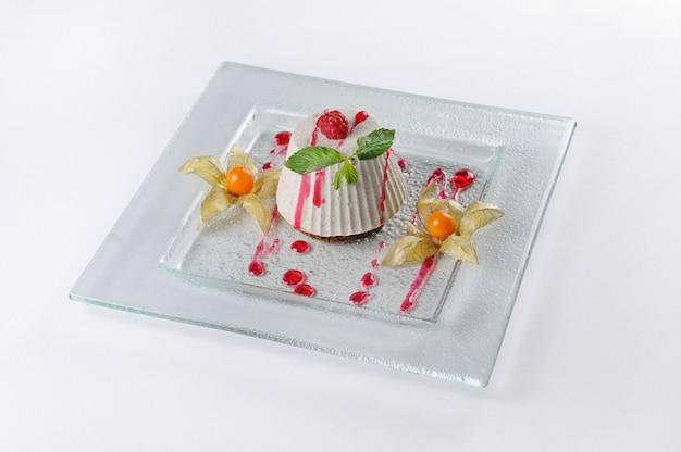Tiro isolado de uma sobremesa com framboesas e physalis