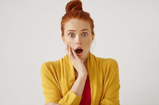 Tiro isolado interior de mulher atraente ruiva jovem chocada com boca de cabelo bun abertura larga aberta e segurando a mão na bochecha, congelada pelo medo, choque ou espanto. conceito de espanto