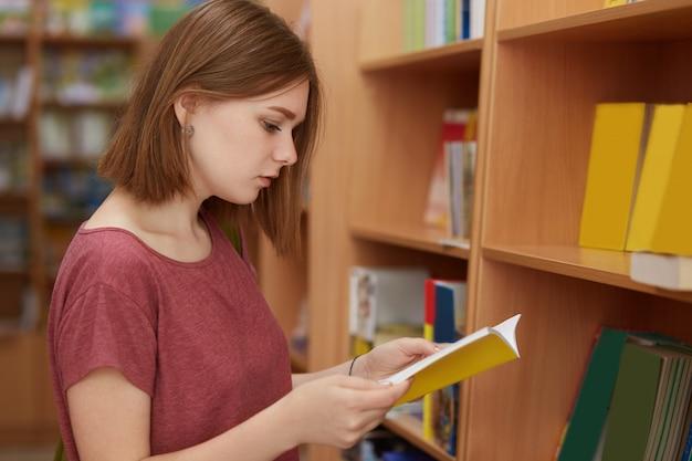 Tiro lateral da estudante universitária séria focada no livro, poses na biblioteca da escola, escolhe a literatura necessária para a preparação do relatório, veste camiseta. adolescentes, estudando e lendo o conceito