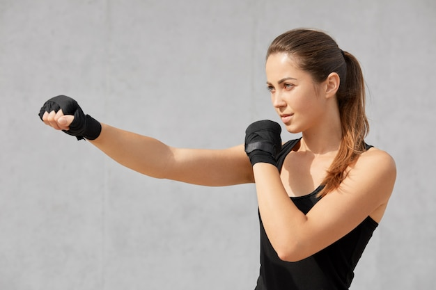 Tiro lateral do boxeador atraente mulher desportivo tem ataduras nas mãos