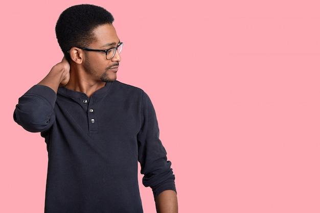 Tiro lateral do gerente afro-americano sério coça o pescoço, concentrado de lado, usa óculos ópticos e blusa casual