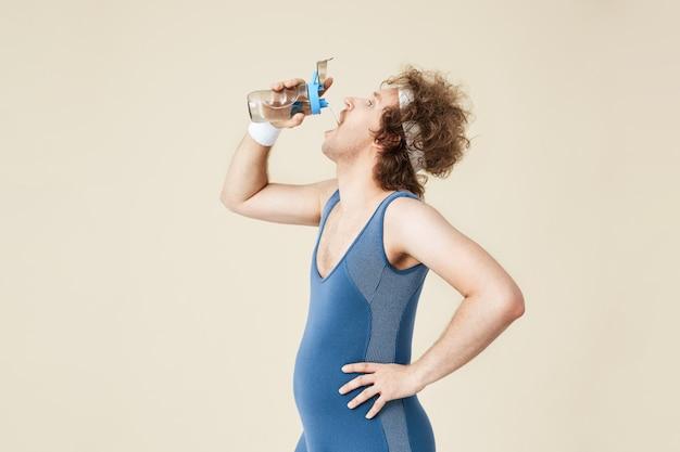 Tiro lateral do homem thursty beber água de garrafa de vidro