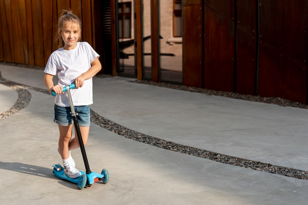 Tiro longo, de, menina, montando, azul, scooter