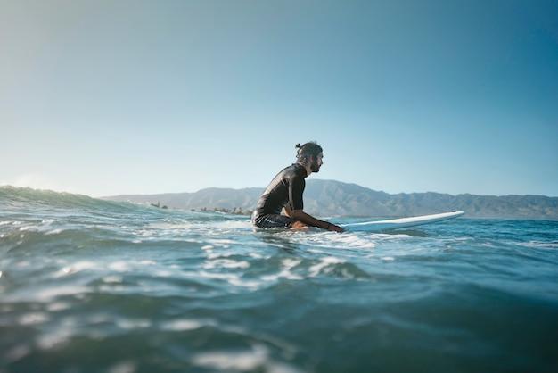 Tiro longo do surfista na água