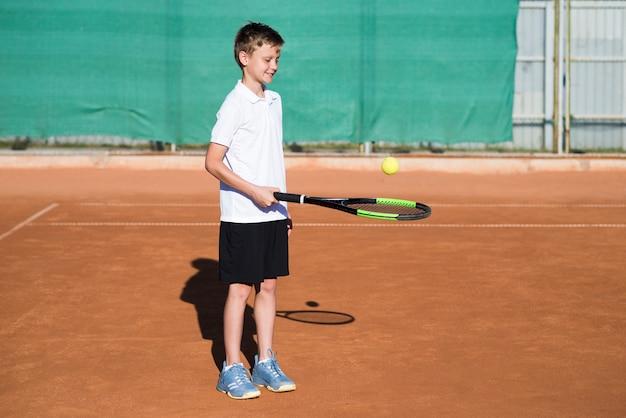 Tiro longo garoto jogando tênis