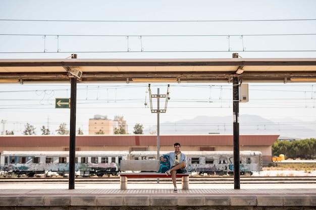 Tiro longo, sorrindo, viajante, esperando, trem