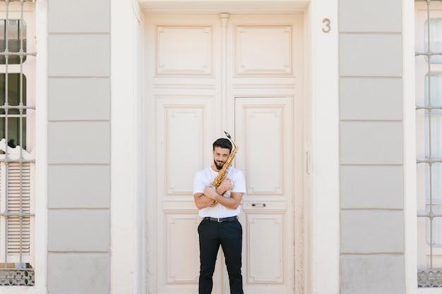 Tiro longo, vista dianteira, homem, abraçando, saxofone