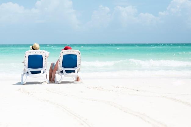 Tiro longo, vista traseira, de, par, sentando, ligado, cadeiras praia