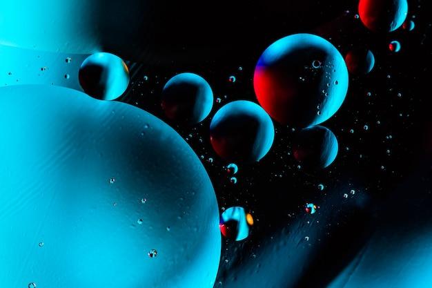 Tiro macro de bolhas de óleo com água no colorido.