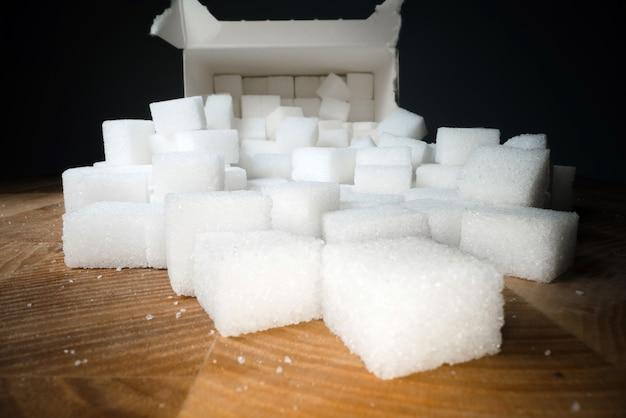 Tiro macro de cubos de açúcar ao lado da caixa da caixa na mesa de madeira. adoçante alimentar não saudável, cubos de cristal doce