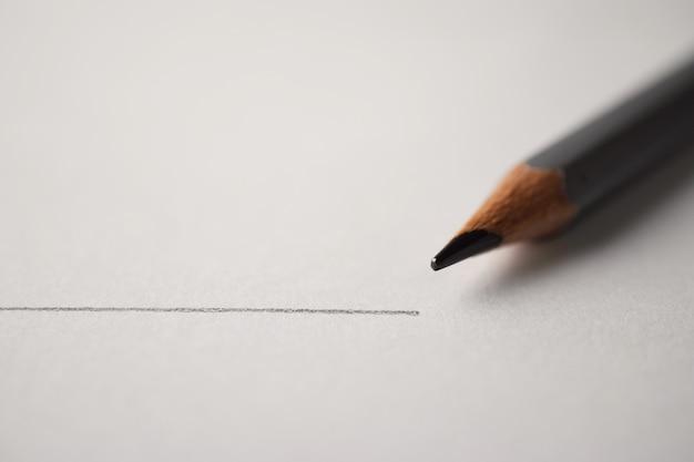 Tiro macro de grafite de lápis preto com linha de desenho em papel branco texturizado
