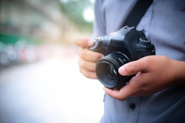 Tiro macro de mãos de homem segurando a câmera fotográfica