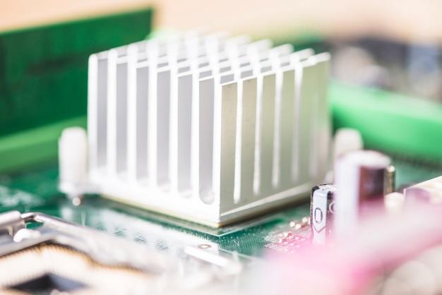 Tiro macro do dissipador de calor branco no circuito da placa-mãe