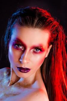 Tiro macro do rosto de mulher bonita com maquiagem artística. retrato de arte da moda.