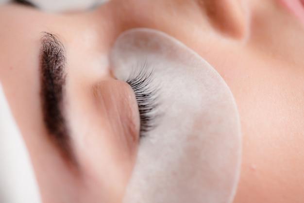 Tiro macro linda de olhos femininos com cílios longos extremos e maquiagem delineador preto.