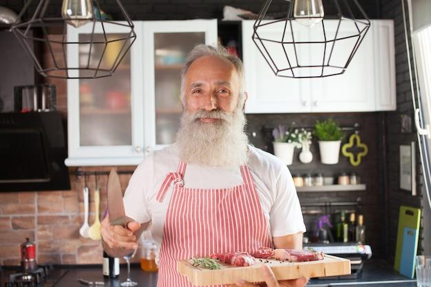 Tiro meados de sorridente chef maduro com placa de corte na mão. carne deitada no quadro. homem isolado na cozinha moderna bem organizada.