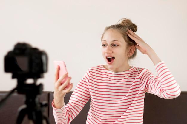 Tiro médio animado blogueiro com telefone