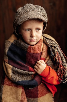 Tiro médio bonito garoto com cachecol e chapéu
