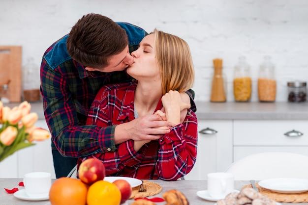 Tiro médio casal a beijar na cozinha