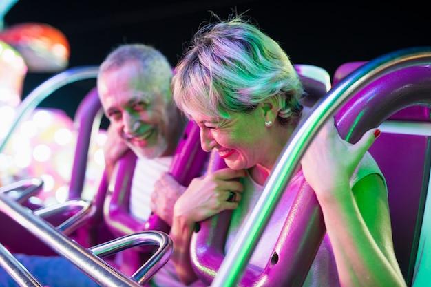 Tiro médio casal adulto em passeio de diversões