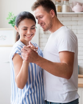Tiro médio casal dançando dentro de casa