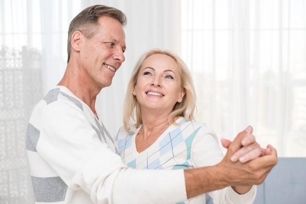 Tiro médio casal dançando na sala de estar