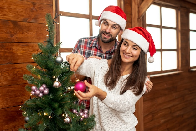 Tiro médio casal feliz a decorar a árvore de natal