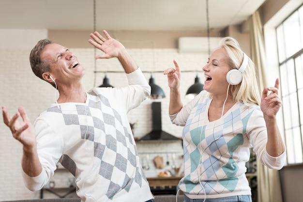 Tiro médio casal feliz com fones de ouvido dentro de casa
