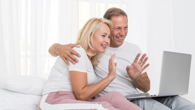 Tiro médio casal feliz com laptop acenando