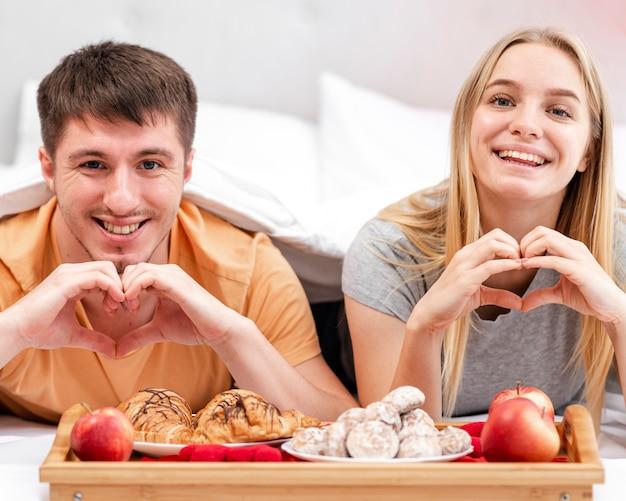 Tiro médio casal feliz em forma de coração gesto com a mão