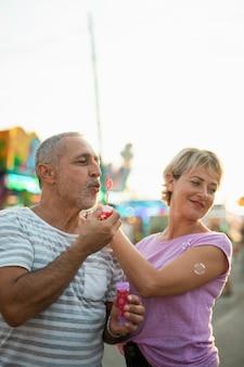 Tiro médio casal feliz fazendo bolhas de sabão