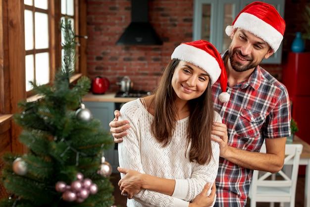 Tiro médio casal feliz olhando para a árvore de natal